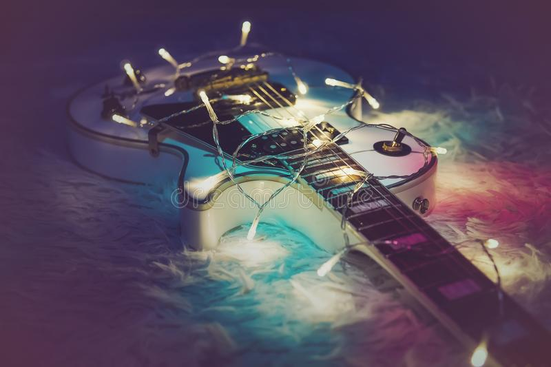 Guitar with lighted garland. Electric guitar with lighted garland. New year gift in the form of expensive electric guitars. Gift for the musician on Christmas. A royalty free stock photos
