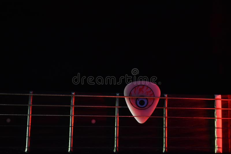 Electric guitar neck with a cool guitar pick in dark background stock photos