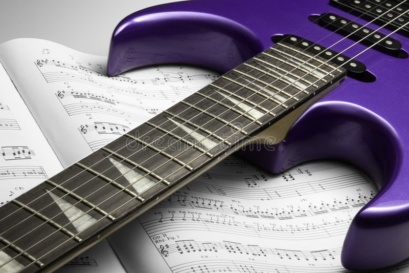 Electric Guitar on Sheet Music. A purple electric guitar on top of an open sheet music book stock photography
