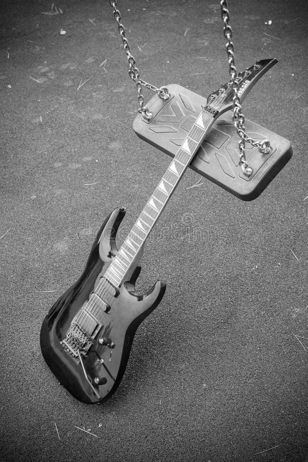 Swing genre concept. An electric guitar on a swing, a genre concept stock image