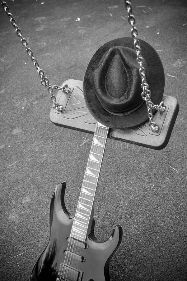 Swing music, a concept. Electric guitar on a swing, a music genre concept stock photography