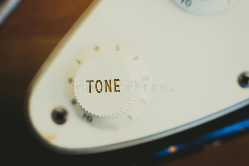 Electric guitar tone knob detail, music symbol. Electric guitar tone knob detail vintage light effect and selective focus, view from the top stock photo