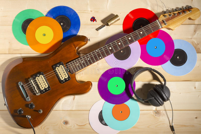 Electric guitar, 33 and 45 vinyl records, and headphones. A young vintage musician bedroom. Electric guitar, 33 and 45 vinyl records, and headphones stock image