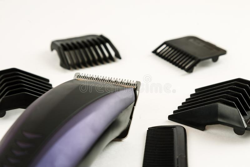 Electric hair clipper with different size attachments on a white background. Trimmer, clipping, closeup, accessory, hairstyle, haircut, machine, barber, beauty royalty free stock photo