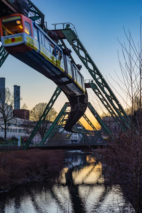 Electric hanging train moving over the wupper river stock image