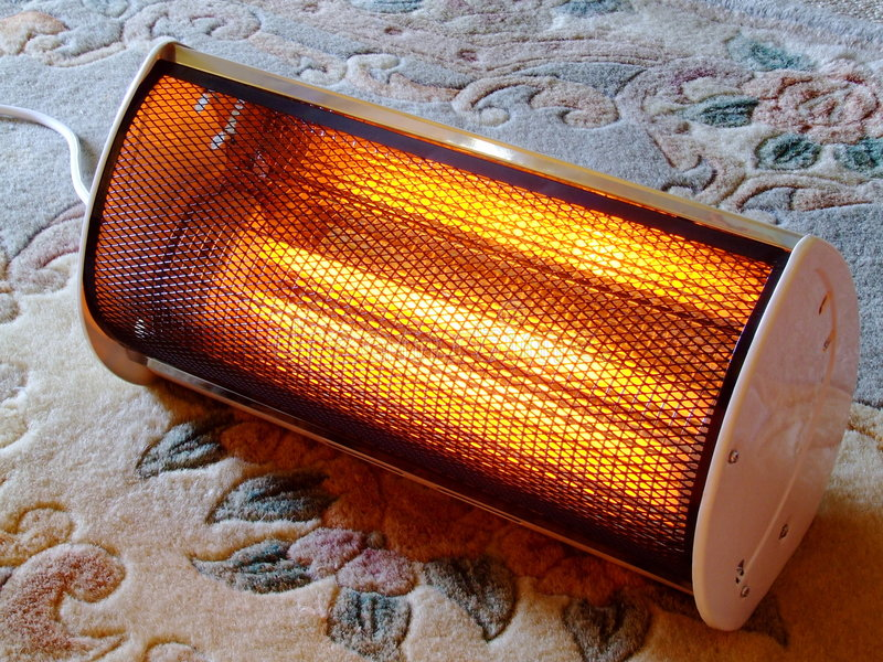 Electric Heater. Close-up of a small radiant electric heater on a rug stock photo