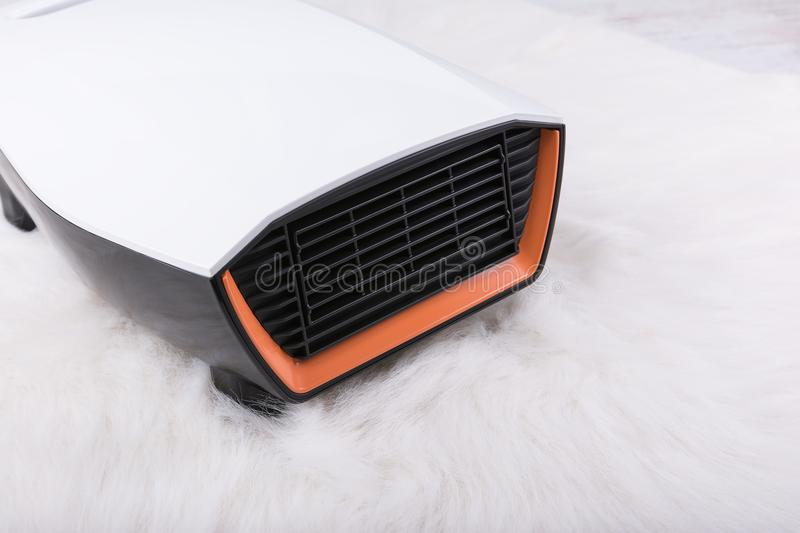 Electric heater on white furry carpet. Winter background stock photo