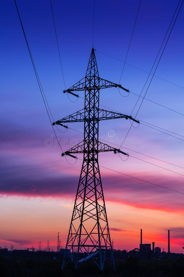 Electric high voltage power post with plant factory in the background at sunset. / sunrise royalty free stock images