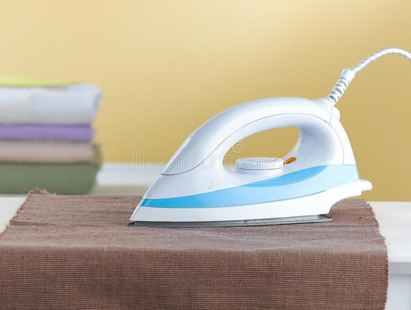 Electric iron isolated in the laundry room stock photo
