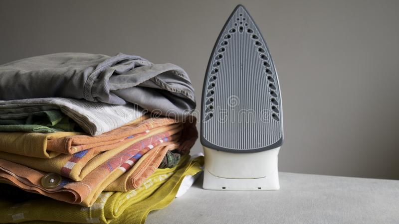 Electric iron and pile of clothes.  stock photos