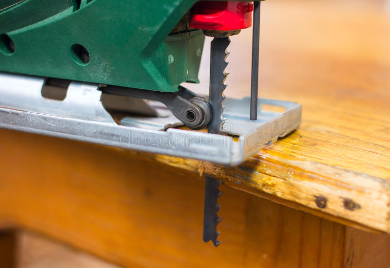 Electric jigsaw cutting a piece of wood stock photo