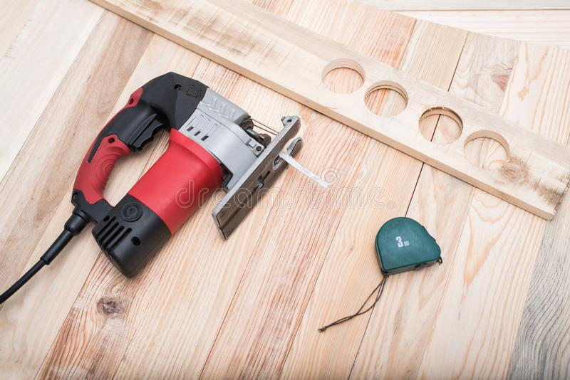 Electric jigsaw, measuring tape and workpiece lying on a light brown wooden table. Woodworking. Close up.  stock images