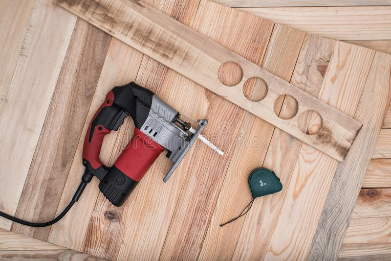 Electric jigsaw, measuring tape and workpiece lying on a light brown wooden table. Woodworking. Close up, directly above royalty free stock photography