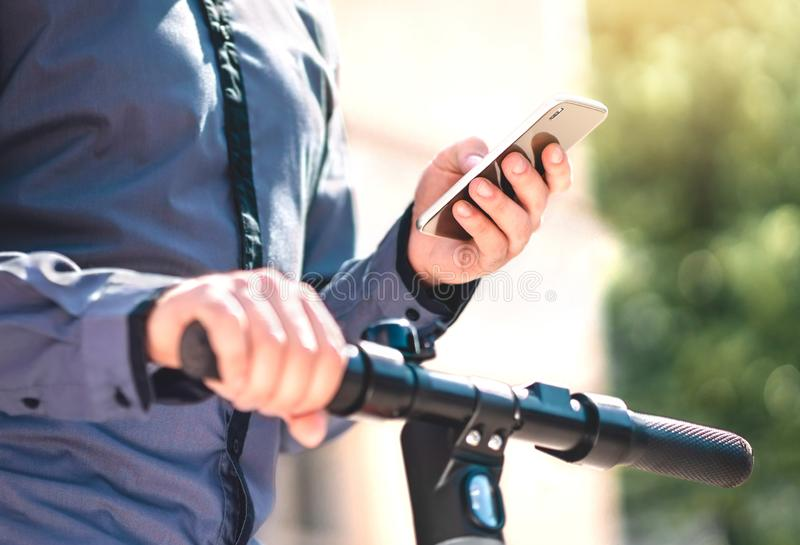 Electric kick scooter rental app in phone. Man using smartphone to rent an e vehicle to commute. royalty free stock photos