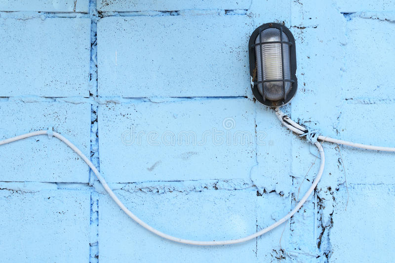 Electric lamp. On blue brick wall background royalty free stock photos