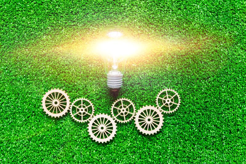 Electric light bulb, gears on the background of artificial green grass. stock photo