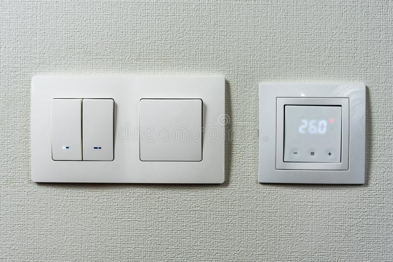Electric light switch and socket on the empty wall, electrical power socket and plug switched. Comfort house. the sensor for floor. Heating shows the stock photos