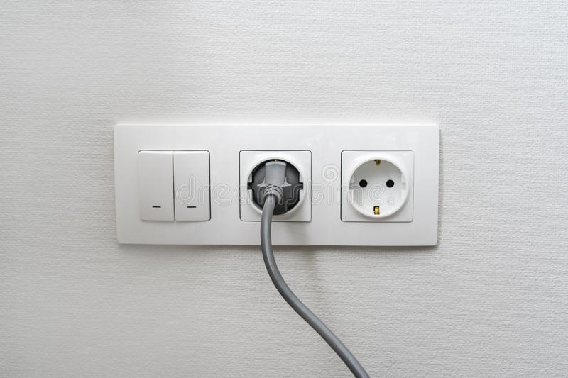 Electric light switch and socket on the empty wall, electrical power socket and plug switched. The concept of energy savings.  royalty free stock image