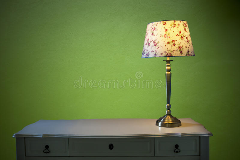 Electric lighting lamp on white table with emerald green cement wall background. File of electric lighting lamp on white table with emerald green cement wall stock images