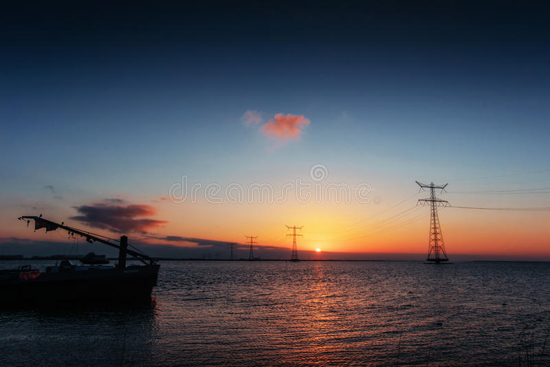 Electric line above water during a fantastic sunset. Electric line above water during a fantastic sunset stock images