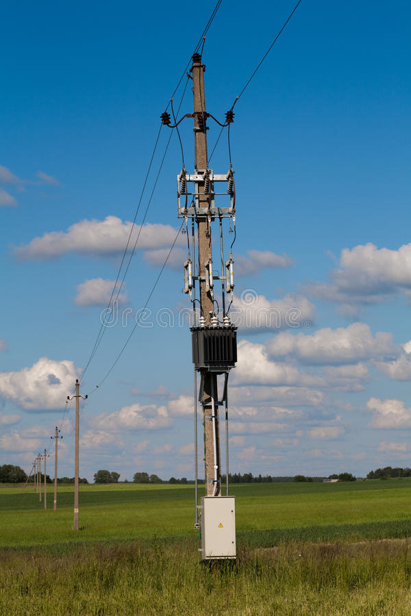 Electric line in green fields. Vintage Electric power-line in green fields against blue cloudy sky stock photography