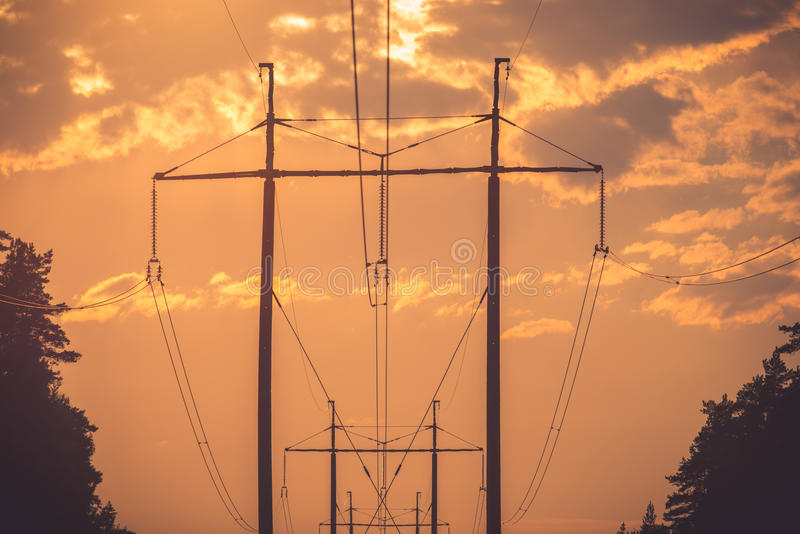Electric line. Over the cloudy sunset sky stock photography
