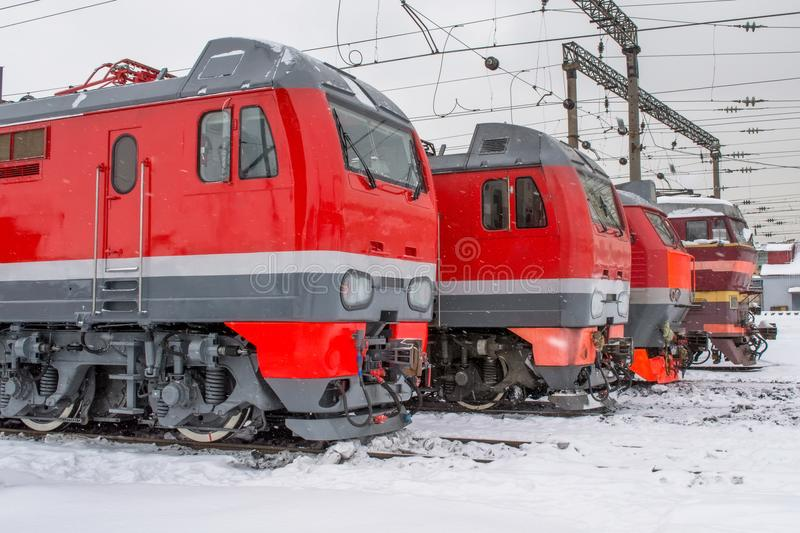 Electric locomotives are lined up on the railway in winter snow depot. royalty free stock photography