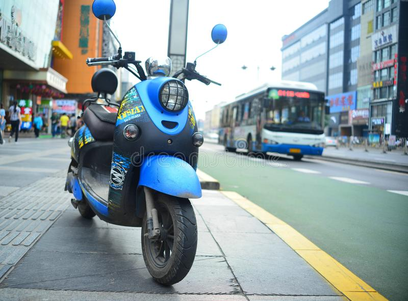 An electric motorcycle parked on the streets of the city. An electric motorcycle parked on the streets of Xi`an city.nAn electric bus passed by.nNew energy royalty free stock images