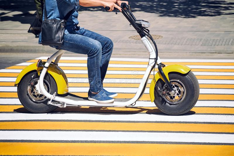 An electric motorcycle, scooter, or bicycle rides in the city. An electric motorcycle, scooter, or bicycle rides in the city on the road through a pedestrian stock photos