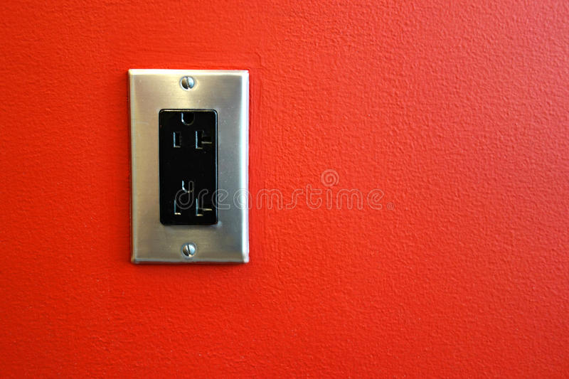 Electric Outlet. An electric outlet mounted on a red wall stock images