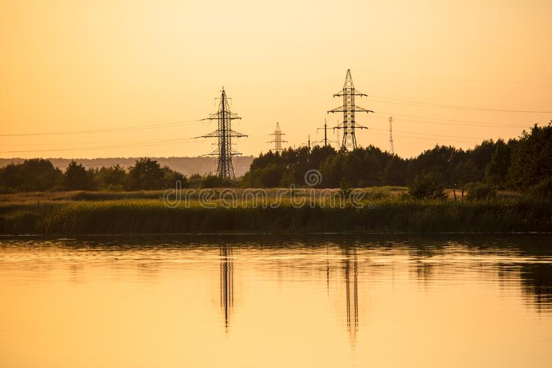 Electric pillar with reflection in the water at sunset.  royalty free stock image