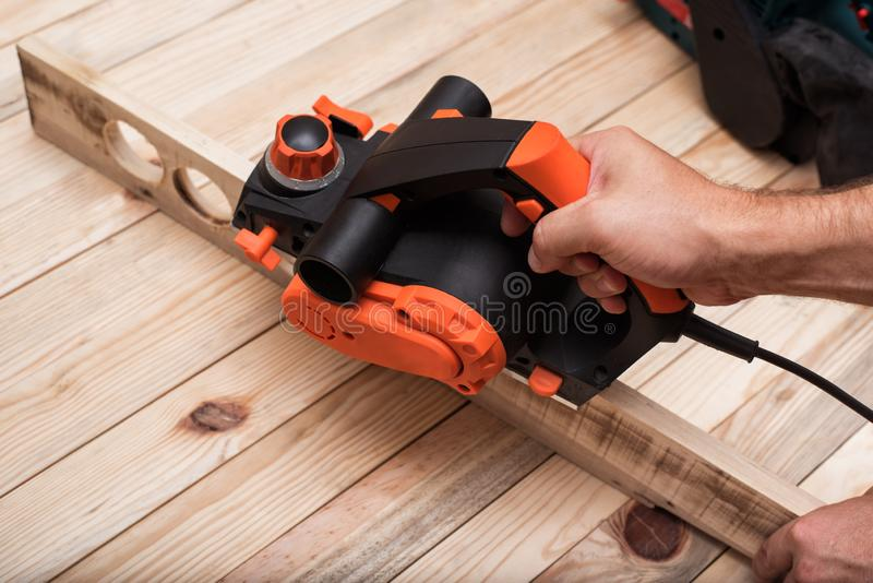 Electric planer in male hand. Processing of the workpiece on light brown wooden table.  stock images