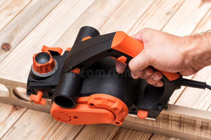 Electric planer in male hand. Processing of the workpiece on light brown wooden table. Close up. Electric planer in male hand. Processing of the workpiece on royalty free stock image