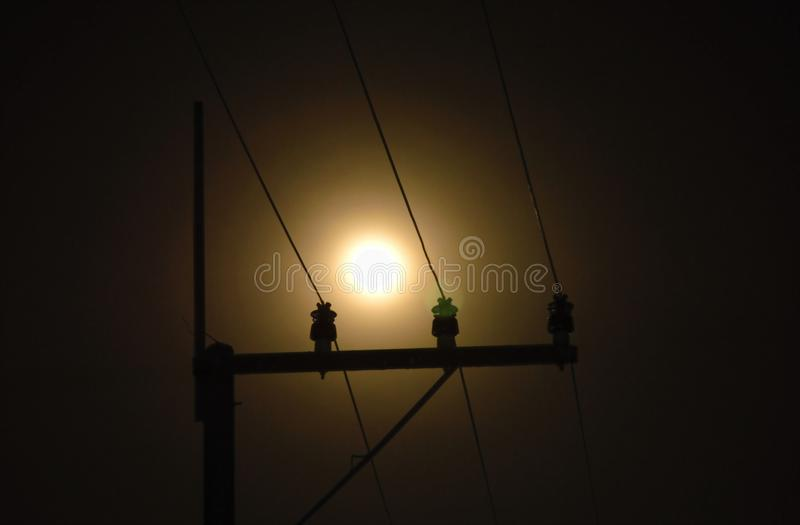 Electric pole and cable with full moon background in night royalty free stock photography