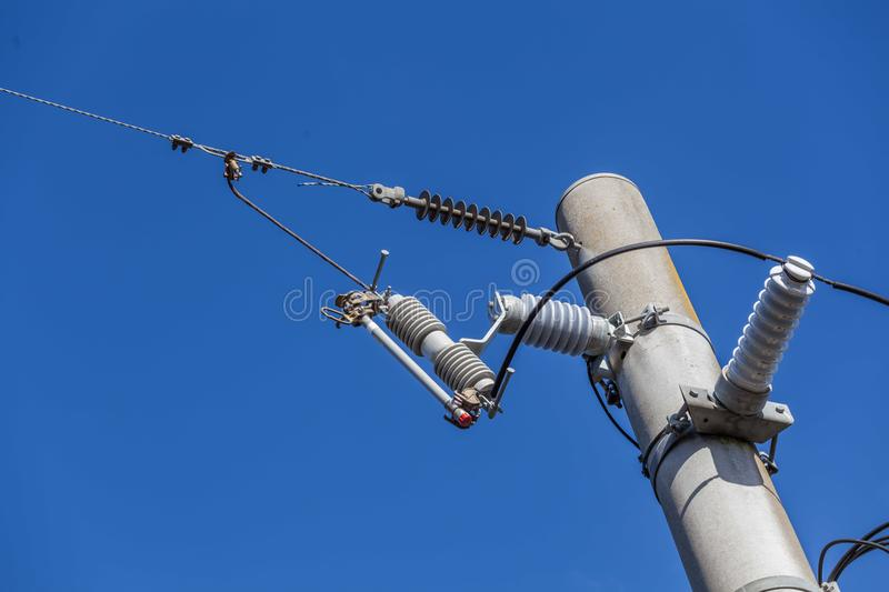 Electric pole with high voltage wires and isolators on blue sky with copy space. royalty free stock photography