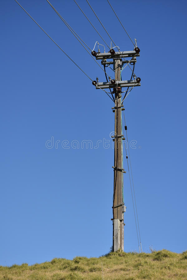 Electric pole on hill. A lone concrete electric pole on a hill stock photos