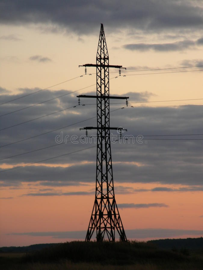 Electric pole, tower, against the background of evening clouds stock photo