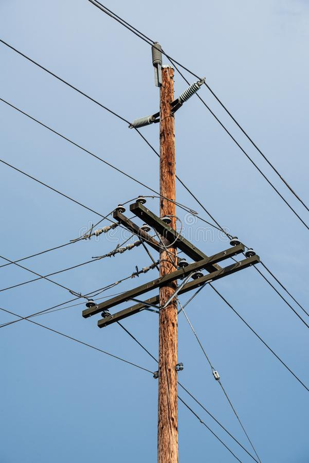 Electric pole and wires, wood electricty pole on blue sky background. stock photography