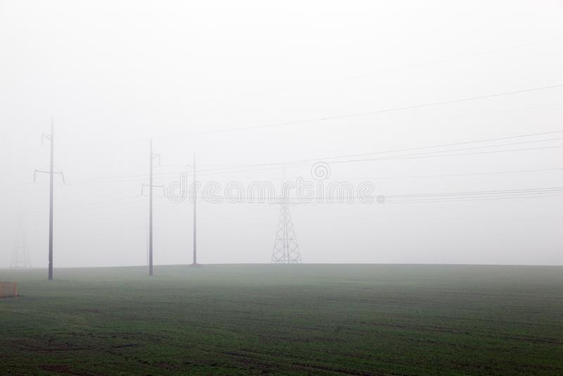 Electric poles in the mist royalty free stock image
