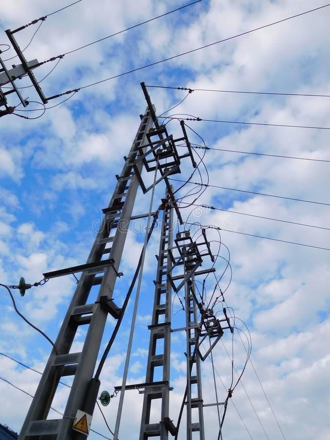 Electric poles, power lines on a background of blue sky and clouds royalty free stock photo