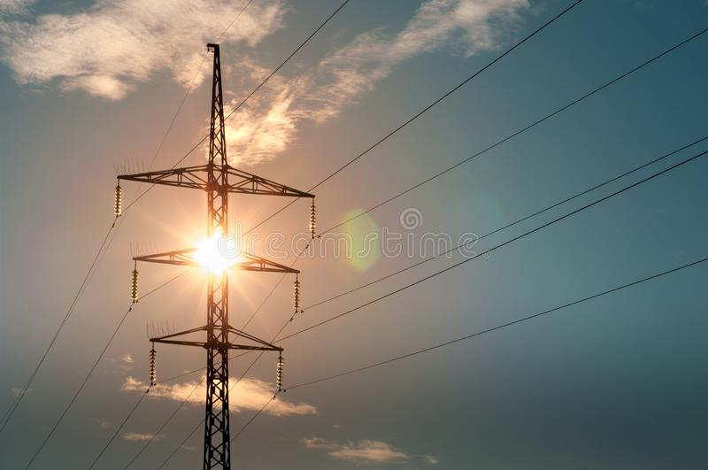 The electric poles supporting wires on blue sky background. Power line with tower on sun background royalty free stock photography