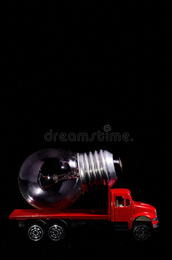Red Truck Light Bulb. Electric Power Concept Red Truck and Light Bulb on a Black Background stock photography