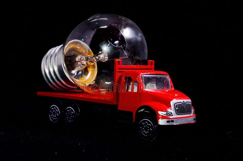 Red Truck Light Bulb. Electric Power Concept Red Truck and Light Bulb on a Black Background stock image