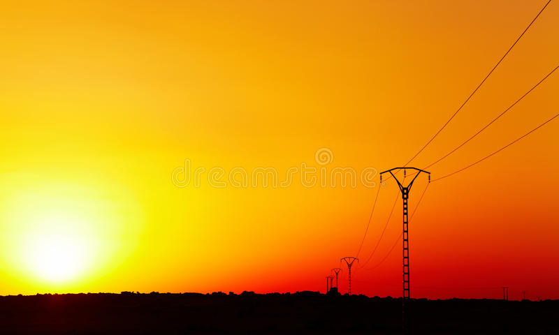 Electric power line against colorful sky at sunset. Electric power line in Sahara Desert against colorful sky at sunset stock images