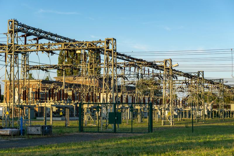 Electric power line in a field - voltage transformation substation. Blue sky royalty free stock images