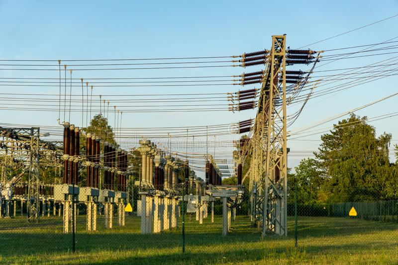 Electric power line in a field - voltage transformation substation. Blue sky stock image