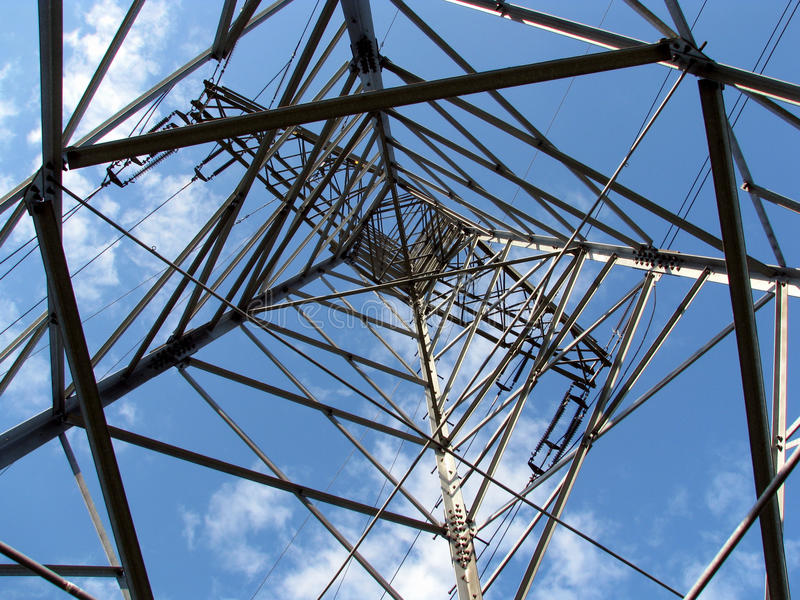 Electric power line tower. Details of a tall steel electric power transmission line tower stock photography