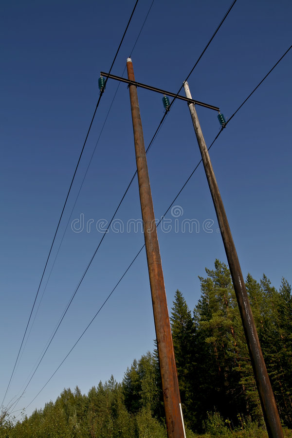 Electric power lines. On wooden poles in a rural scenery royalty free stock photos