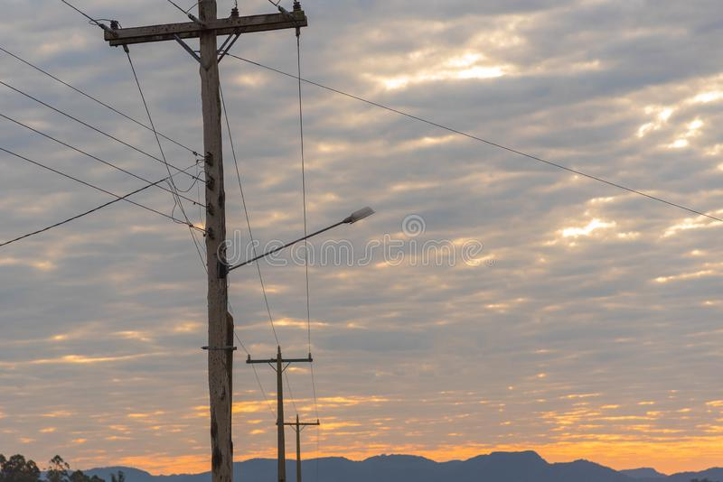 Electric power poles at dawn of the day stock photo