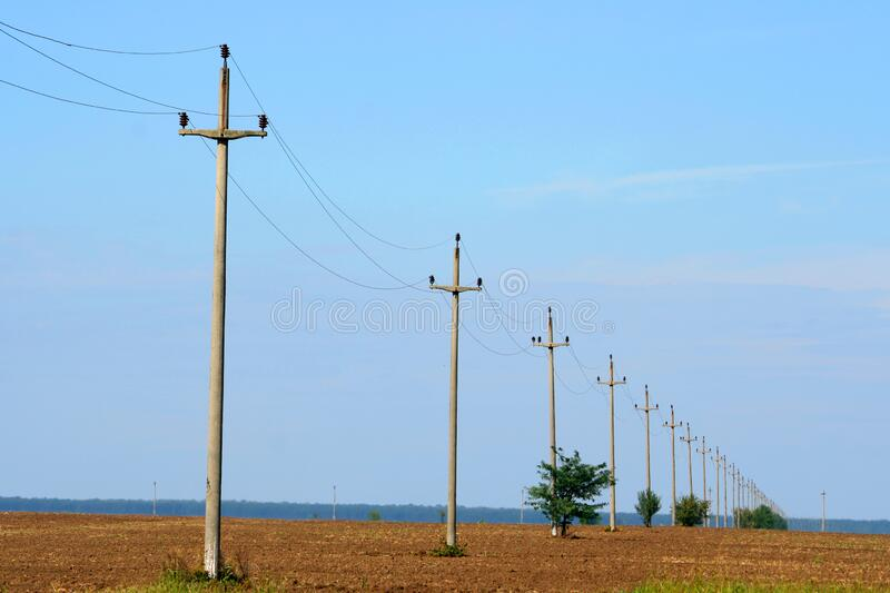 Electric power poles on the field. Straight line of electric power poles lined up on the field stock photos